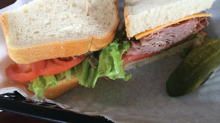 """""""The Queens"""" Roast Beef ($6.45), comes with piles of roast beef, along with cheddar cheese, tomato and lettuce on sourdough bread"""