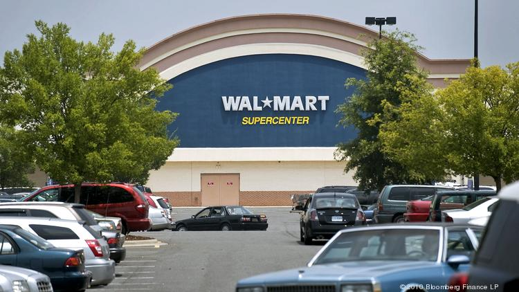 Customers drive through the parking lot of a Wal-Mart Supercenter store.