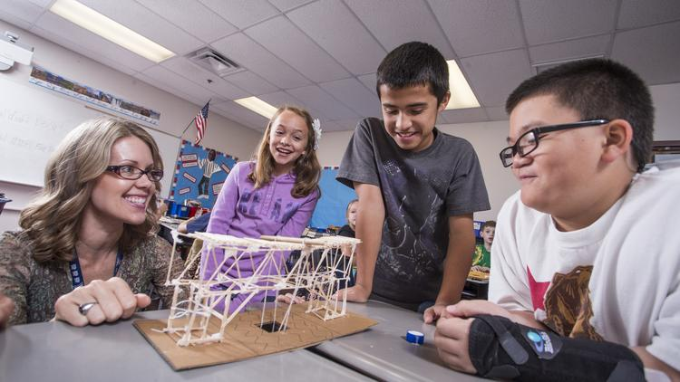 Beth Maloney, a teacher at Sunset Hills elementary School in Surprise, works with students, from left, Kristen Hatcher, Xavier Ponce and Marki Hesse on a lesson building a bridge with toothpicks. the lesson in math and engineering requires a boat to be able to pass beneath the bridge and a car to be able to pass over the bridge.