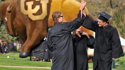 University of Colorado Boulder graduates high-five each other while gathering at the Norlin Quad before the processional leading to the graduation ceremony at Folsom Field.
