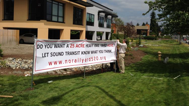 Opponents of a plan by Sound Transit to build a large light-rail maintenance base erected a banner Thursday at the Plaza 520 business park in Bellevue. Plaza 520 is one of four sites that Sound Transit is considering for the base.
