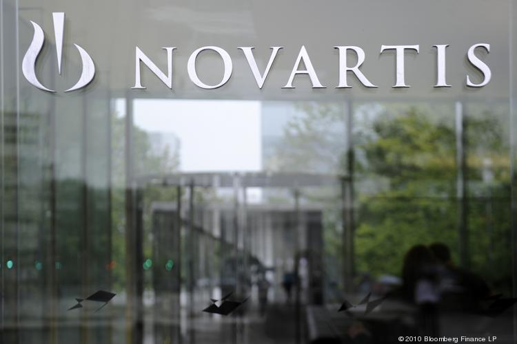 "The Novartis AG logo is seen on the company's headquarters in Basel, Switzerland, on Thursday, Aug. 12, 2010. Novartis AG won European Union approval to acquire a majority stake in Alcon Inc., the world's largest eye-care company, from Nestle SA after it offered to sell ""a number of businesses,"" to allay competition concerns about the deal. Photographer: Adrian Moser/Bloomberg"