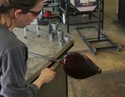 Quade uses tongs to cut the object from the glass-blowing tube.