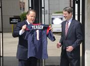 Houston Texans President Jamey Rootes (left) presents J. Michael Yeager, BHP Billiton Petroleum CEO, with a Texans jersey. BHP signed a new sponsorship deal with the Texans and the Houston Livestock Show and Rodeo.
