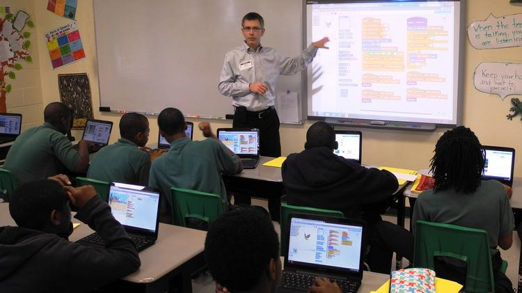 Academy Prep's seventh grade students learn basic computer programming skills from Syniverse Inc. employees.