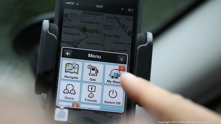 An automobile driver uses Waze's map software, displayed on an Apple iPhone 5 in 2013.