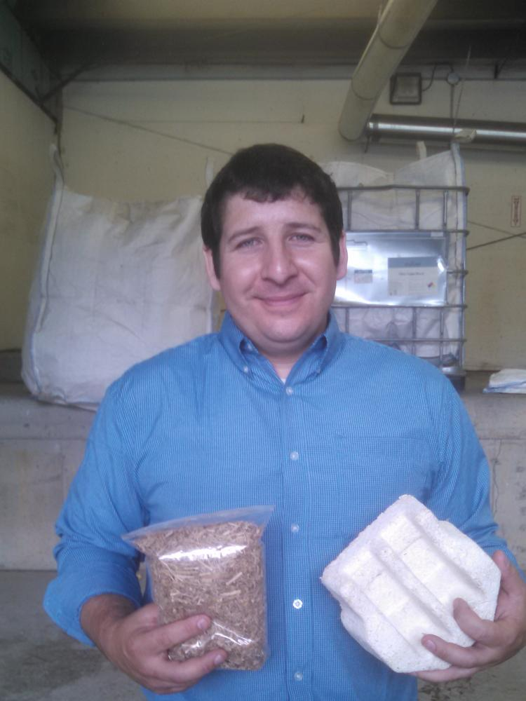 Justin Frisino, Ecovative vice president of materials supply, holds corn stover, a by-product of ground up corn stalks and leaves. The stover is used along with mushrooms to create the biodegradable packaging alternatives to foam and plastic.