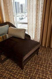 A setee sits on decorative carpet design in a corner of the bedroom of the Presidential Suite.