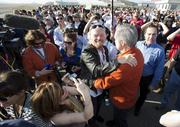"""Sir Richard Branson hugs designer Burt Rutan as they are surrounded by employees of Virgin Galactic. The SpaceShip Company and Scaled Composites watch as Virgin Galactic's SpaceShip2 streaks across the sky under rocket power, its first ever since the program began in 2005. Burt's wife Tonya Rutan is at right taking their picture. The spacecraft was dropped from its """"mothership,"""" WhiteKnight2, over the Mojave, CA area, April 29, 2013 at high altitude before firing its hybrid power motor. Virgin Galactic hopes to become the first commercial space venture to bring multiple passengers into space on a regular basis."""