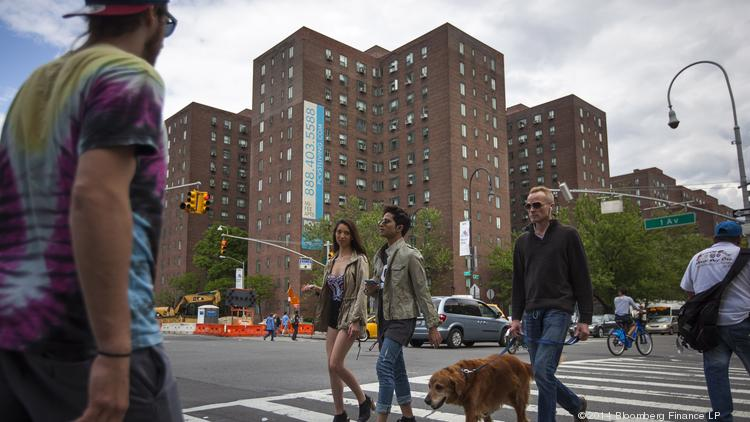 Pedestrians cross the street in front of Stuyvesant Town-Peter Cooper Village, Manhattan's largest apartment complex.
