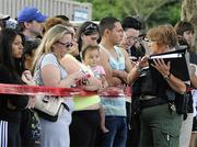 A police officer explains to parents how they are to be reunited as students arrive by bus at a shopping center parking lot in Wood Village, Ore., after a shooting at Reynolds High School Tuesday, June 10, 2014, in nearby Troutdale. A gunman killed a student at the high school east of Portland Tuesday and the shooter is also dead, police said.(AP Photo/Greg Wahl-Stephens)