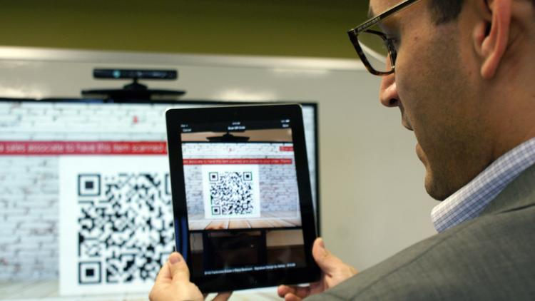Luis Rodriguez, senior director of software development at High Touch, demonstrates how a retail staff member might scan a product QR code with High Touch's corresponding iPad app. Staff could then complete the transaction on the iPad.