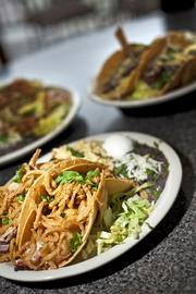 A beef brisket taco dish from Tumbleweed can be seen in the foreground, with grilled steak and avocado chipotle chicken dishes in the background.