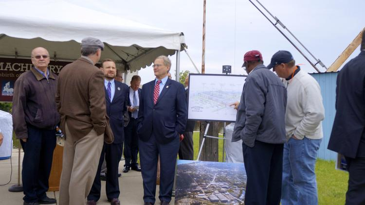 A number of elected officials examine the newly unveiled Machinery Row project in Racine on Tuesday.