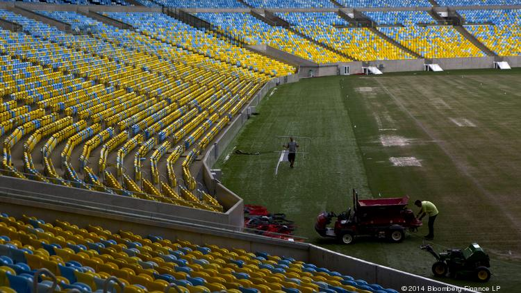 Workers make final preparations to the field at Maracana Stadium in Rio de Janeiro, Brazil. The World Cup kicks off today. Photographer: Dado Galdieri/Bloomberg