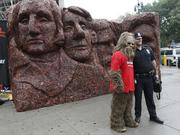 "Jack Link's mascot Sasquatch and an NYPD officer pose in front of ""Meat Rushmore."""