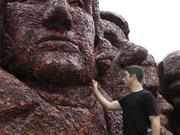 "Artist Alex Valhouli puts the finishing touches on ""Meat Rushmore."""