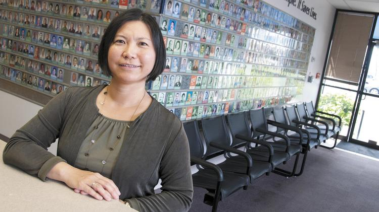 Blood Bank of Hawaii President and CEO Dr. Kim-Anh T. Nguyen stands in front of The Wall, which features donors who have given the most blood over the years.