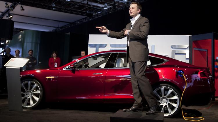 Elon Musk, chairman and chief executive officer of Tesla Motors Inc., speaks in front of a Tesla Model S electric car on day two of the 2010 North American International Auto Show in Detroit, Michigan, U.S., on Tuesday, Jan. 12, 2010.