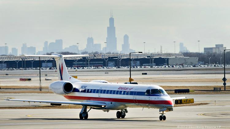 The skyline of Chicago behind an American Airlines Inc. Embraer EMB-145LR aircraft as it travels on the tarmac at O'Hare International Airport in Chicago.