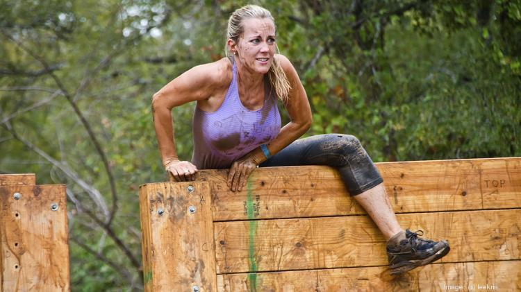 An unidentified female race participant climbs over a wooden wall obstacle in the Dash of the Titans Mud Run Race in Dallas.