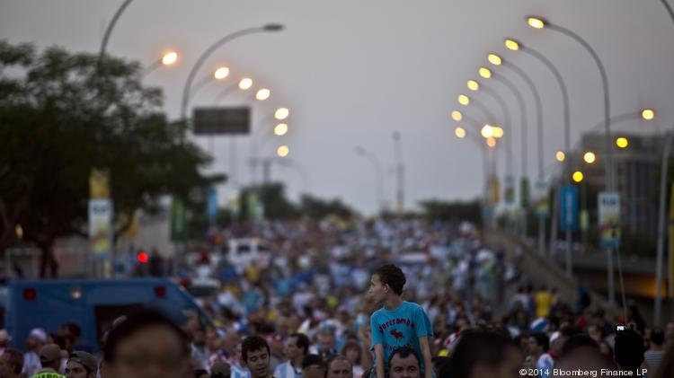 Fans walk to Maracana stadium before a match between Argentina and Bosnia and Herzegovina on Sunday. The Maracana is the spiritual home of Brazilian soccer, where record attendance was attained in 1950 when Brazil lost to Uruguay in the Cup finals. Photographer: Dado Galdieri/Bloomberg