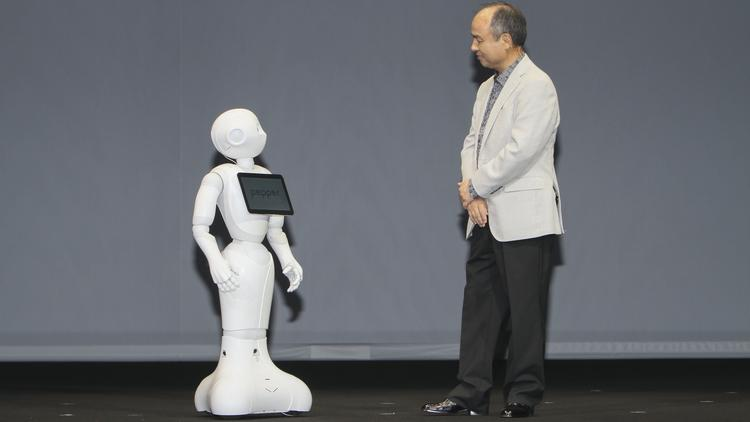 """SoftBank CEO Masayoshi Son interacts with his company's robot, """"Pepper,"""" during a recent press conference. Son recently announced that SoftBank, which owns more than 80 percent of Overland Park-based Sprint Corp., will offer the robot to consumers in February 2015."""