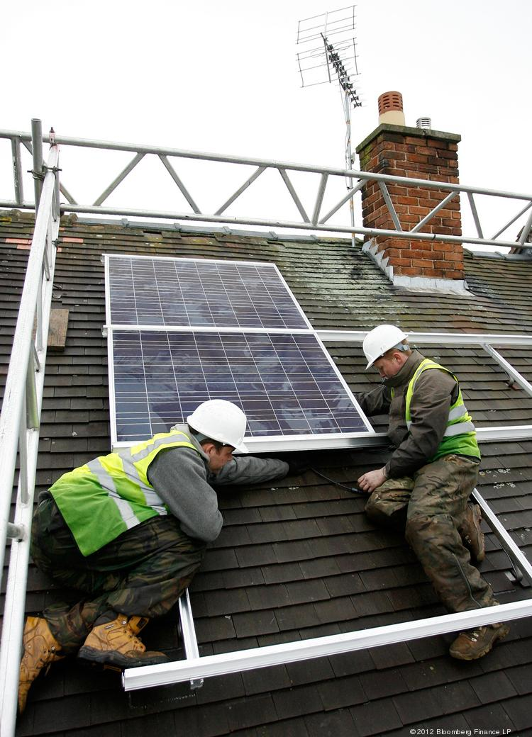 Workers installing solar panels on a house.
