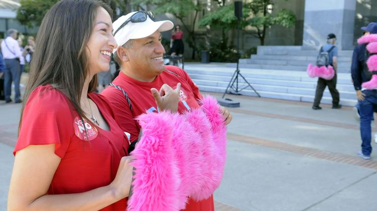 Sherry Martinez and Giovanni Bronzo hold up a signature pink Lyft mustache at a rally at the State Capitol for ridesharing services such as Lyft and Uber.