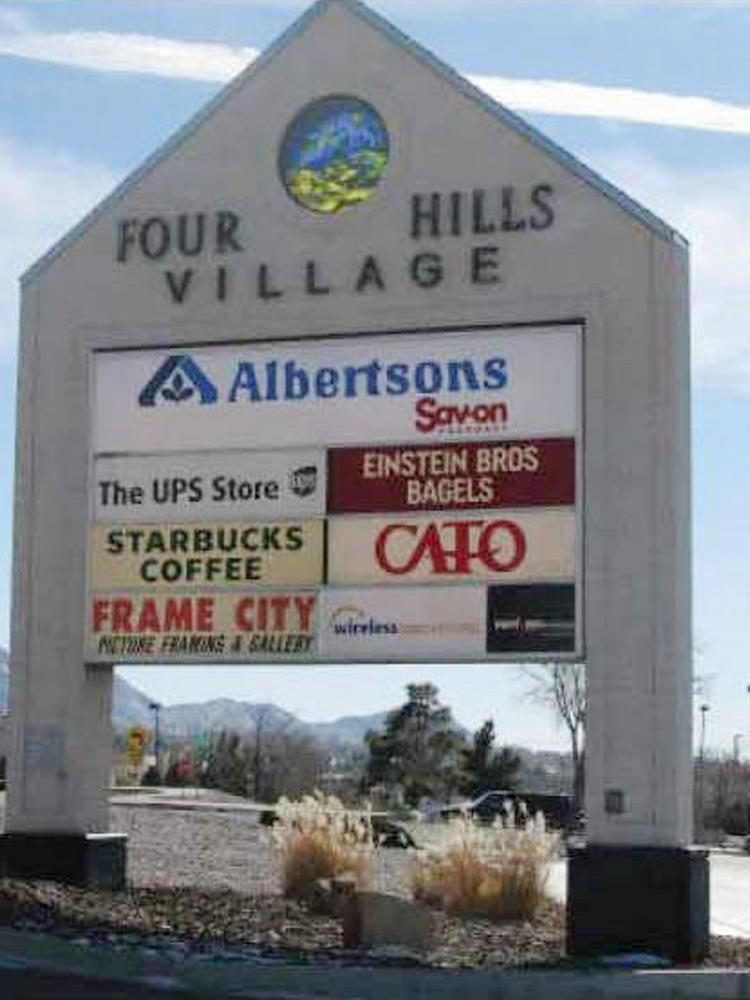 Two high-profile Albuquerque shopping centers are listed for sale on an online auction. Pictured is the sign at Four Hills Village Shopping Center, which is listed at a starting bid of $1.25 million on auction.com.