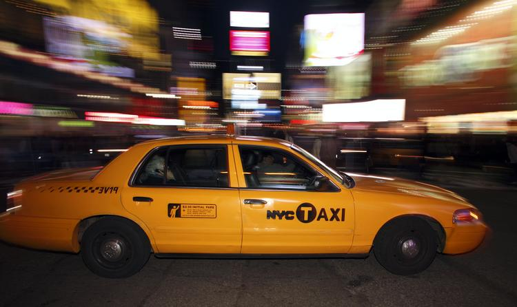 A New York City taxi drives through Times Square in New York.