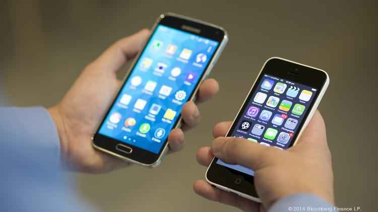 A Samsung Electronics Co. Galaxy S5 smartphone, left, and Apple Inc. iPhone 5c are held for a photograph.