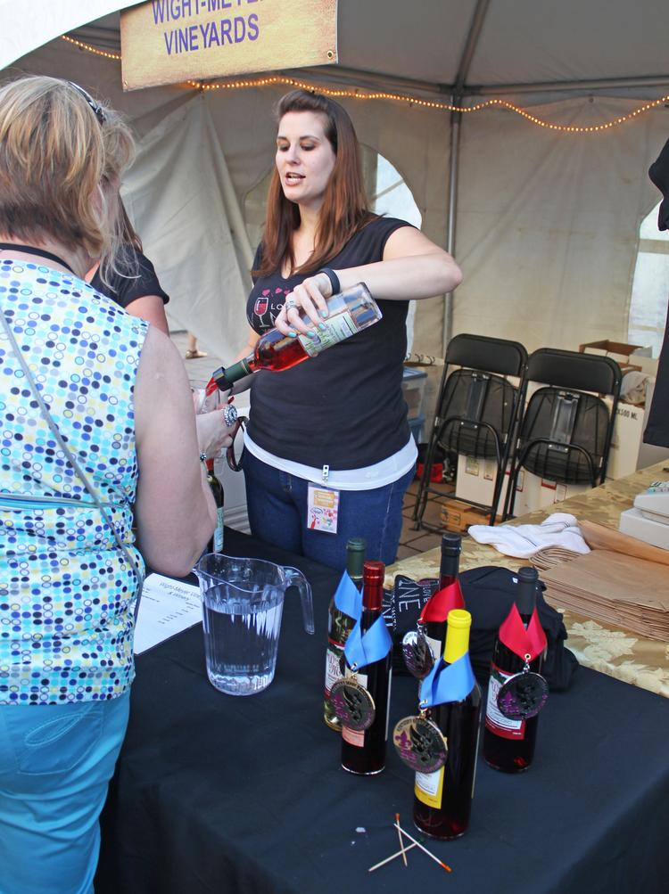 Bridgette Branham, an employee of Wight-Meyer Vineyards & WInery in Shepherdsville, served a WineFest patron at the 2013 event.