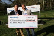 On April 13, employees of NewDay USA, one of the nation's leading mortgage companies serving veterans, gathered at the Vietnam Veterans Memorial to help wash the wall, one of the services provided by the nonprofit Vietnam Veterans Memorial Fund. More than 90 people took part. Shown here are Jan Scruggs, left, and Rob Posner with a $1 million check presented to the fund by the NewDay USA Foundation.
