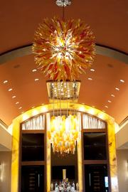 This glass light fixtures hangs over a seating area near the bar area.