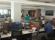 Charlotte Business Journal staffers unpack boxes at a new office in the NASCAR Plaza.