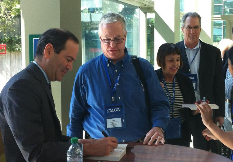 """Neil Barofsky, the former inspector general of the Troubled Asset Relief Program, signs copies of his book, """"Bailout,"""" at the Investment Management Consultants Association annual conference at the Washington State Convention Center in Seattle on Wednesday."""