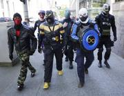 Members of the Rain City Superhero Crime Fighting Movement, including frontman Phoenix Jones (center), patrol Second Avenue in downtown Seattle during their effort to thwart May Day crime on May 1, 2013.