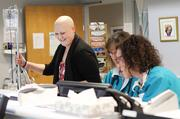 Breast cancer patient and Bellevue school teacher Aubrei McGinn (left) laughs while wheeling around her IV bag past the oncology nurses station at Swedish/Edmonds.