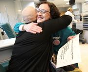 "McGinn (left) gets a hug after she received a ""graduate diploma"" from oncology nurse and fellow cancer survivor Cathy James."