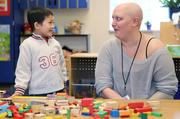 Working mostly three days a week with a mix of full- and part-time days, school teacher Aubrei McGinn talks with a student in April in the Early Learning Program at Stevenson Elementary School in Bellevue. McGinn couldn't afford to take a year off for cancer treatment. More importantly, she needed to continue working, surrounded by children and familiar routines, thinking about something other than treatment.