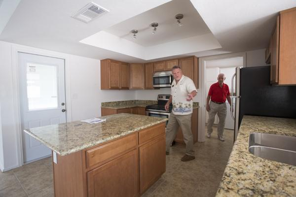 Realtor Jeff Rochford, left, shows a home to potential investor Don Stamper.