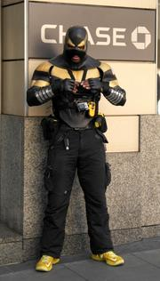 Self-proclaimed superhero Phoenix Jones stands watch at the Chase bank on 2nd Avenue during the 13th Annual May Day March for Workers and Immigrant Rights.