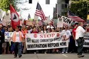 Thousands of people march down 4th Avenue as part of the 13th Annual May Day March for Workers and Immigrant Rights.