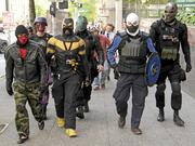 Self-proclaimed superheros Phoenix Jones, third from left, and the Reign City Superhero Crime Fighting Movement patrol on Second Avenue near the Seattle offices of Goldman Sachs on May Day 2013.