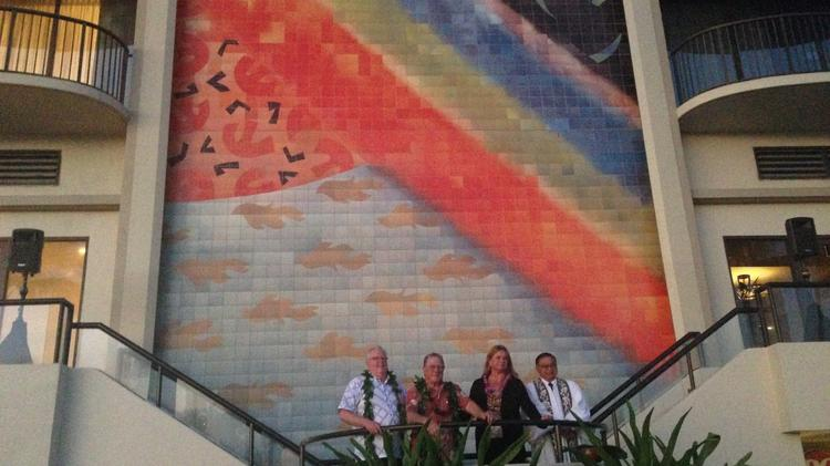 Jerry Gibson, area vice president of Hilton Hawaii; Tony Sheets, son of original mural designer Millard Sheets; Tracy Walker, general manager of the Hilton Hawaiian Village Waikiki Beach Resort; and the kahu pose in front of the renovated rainbow mural.