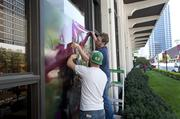 Nic Whitaker and Jordan DeGeorge, on ladder, installed large photographs of women in Derby hats on the exterior of a few windows at The Galt House. They are employees of Sign4.