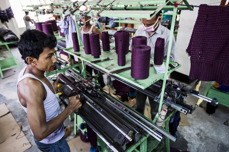 A worker operates a loom on the production line of a garment factory in Bangladesh. The collapse of a building there killed at least 386 workers, prompting varied responses from U.S. and European retailers who have ties to manufacturing operations there.