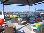 Brightly colored cushions and umbrellas accent the teak-colored furniture at the Embassy Row Hotel's renovated rooftop.