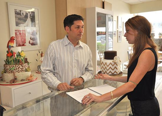 University of Miami student Lisa Weintraub presents a proposal for a new website design to Carlos Martinez, CEO of Miami-based Edda's Cakes.